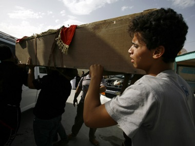 An Iraqi youth mourns as he carries the coffin of a victim of a car bombing in Sadr City. AFP