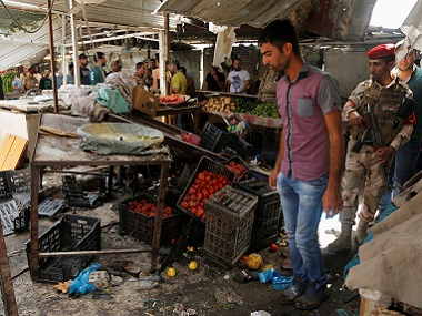 People gather at the site of a suicide bomb attack in a marketplace in Baghdad's al-Shaab district on Tuesday. Reuters
