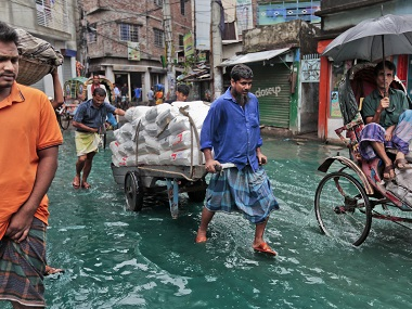 Bangladeshi men pull a loaded cart through a waterlogged street after heavy rainfall in Dhaka. AP