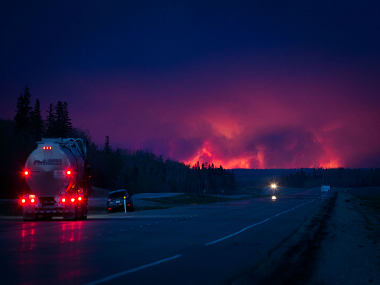 A truck drives on a highway as a wildfire burns south of Fort McMurray, Alberta, Canada. Getty Imags