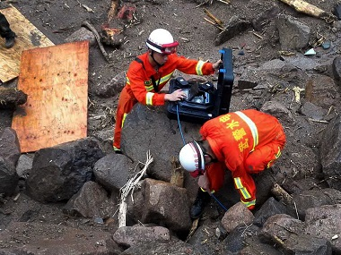 Rescuers use detectors to scan for potential survivors at the site following a landslide in Taining county in southeast China's Fujian province. Chinatopix via AP