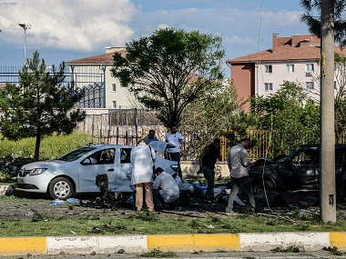 Forensic officers investigate around damaged vehicles on the site where a bomb exploded in Diyarbakir. AFP