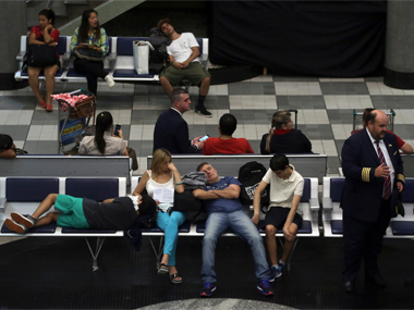 Exhausted travelers rest at an airport. Reuters