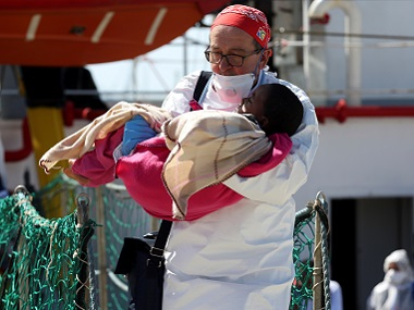 File photo of an MSF doctor carrying a migrant child in Sicily. Reuters