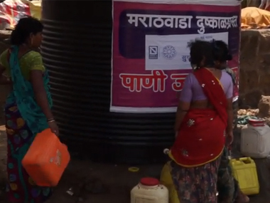 Women wait to fill vessels with water