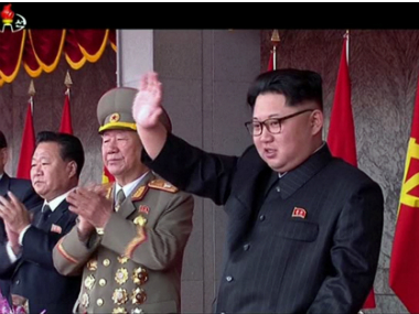 North Korean leader Kim Jong Un, right, waves as people parade to celebrate the first congress of the ruling Workers' Party of Korea in 36 years. AP