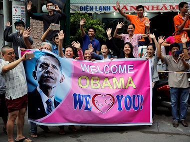 Local residents hold a sign welcoming Obama as he arrives at Ho Chi Minh City. Reuters