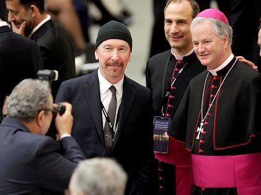 U2 guitarist David Evans, also known by his stage name The Edge, poses with Irish bishop Paul Tighe (R) at the Vatican. Image from Reuters