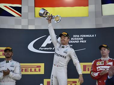 Winner Mercedes AMG Petronas F1 Team's German driver Nico Rosberg (C) celebrates on the podium. AFP