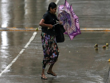 A woman stuggles to hold her umbrella from high wind and rain during a wet day in Colombo , Sri Lanka May 15, 2016. REUTERS/Dinuka Liyanawatte - RTSED7M