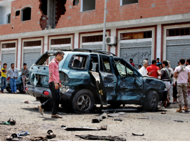 People gather at the scene after a pair of suicide bombings attack in the southern city of Aden in Yemen on Monday. AP