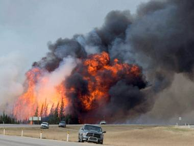 Fort McMurray : A wildfire burns south of Fort McMurray, Alberta, near Highway 63 on Saturday, May 7, 2016. Canadian officials hoped to complete the mass evacuation of work camps north of Alberta's main oil sands city of Fort McMurray on Saturday, fearing the growing wildfire could double in size and reach a major oil sands mine and even the neighboring province of Saskatchewan. AP