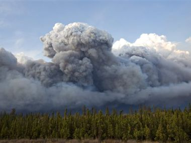 Smoke rises above trees as a wildfire burns in Fort McMurray, Alberta. AP
