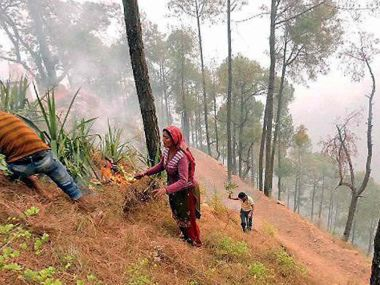 Amola Village : villagers of try to shift safer place after a forest fire in Amola Village in , Yamkeshwal in Uttarakhand on Sunday. PTI Photo ( Best quality available)(PTI5_1_2016_000247B)