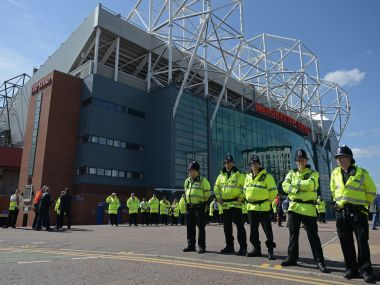Police officers stand on duty outside Old Trafford. AFP