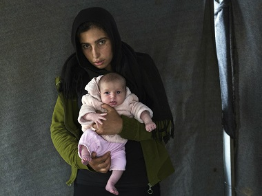 Soumaya Zallaan, a Syrian mother from the city of Deir ez-Zor , poses with her baby girl Ritag. AP