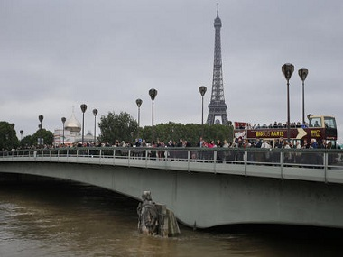 People stand on the Alma bridge. Seine had been at its highest level in nearly 35 years. AP.