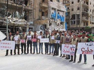 "Syrian activists hold Arabic placards that read, ""Save Aleppo, Aleppo burned, Aleppo is being wiped out,"" during a sit-in in Aleppo, Syria. Civil Defense Directorate in Liberated Province of Aleppo via AP"