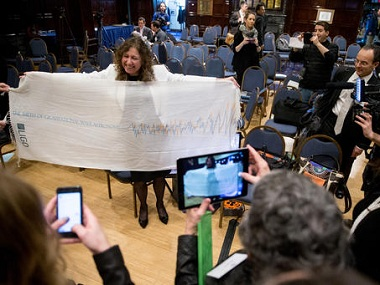 File photo of LIGO spokesperson Gabriela Gonzalez who holds up a scarf depicting gravitational waves. AP.