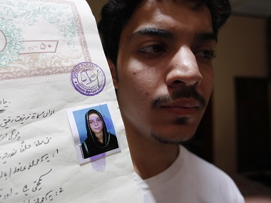 Hassan Khan shows a document with a photograph of his wife Zeenat Bibi. AFP