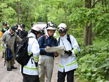 Rescuers search for a 7-year-old boy who is missing in a Japanese forest in Nanae town, on Hokkaido, the northernmost of Japan's four main islands Monday, May 30, 2016. He has been missing since late Saturday afternoon after his parents reportedly made him get out of the car as punishment. (Kyodo News via AP) JAPAN OUT, MANDATORY CREDIT