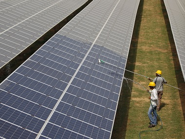 Workers clean photovoltaic panels inside a solar power plant in Gujarat. File photo Reuters