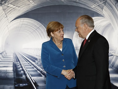 Swiss President Johann Schneider-Ammann (R) shakes hands with German Chancellor Angela Merkel on the opening day of the Gotthard rail tunnel. AFP