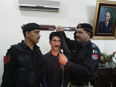 A Pakistani police officer covers the face of the man who allegedly killed Alisha in Peshawar. File photo AP