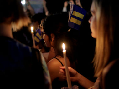People hold a vigil after the Orlando shooting. Reuters
