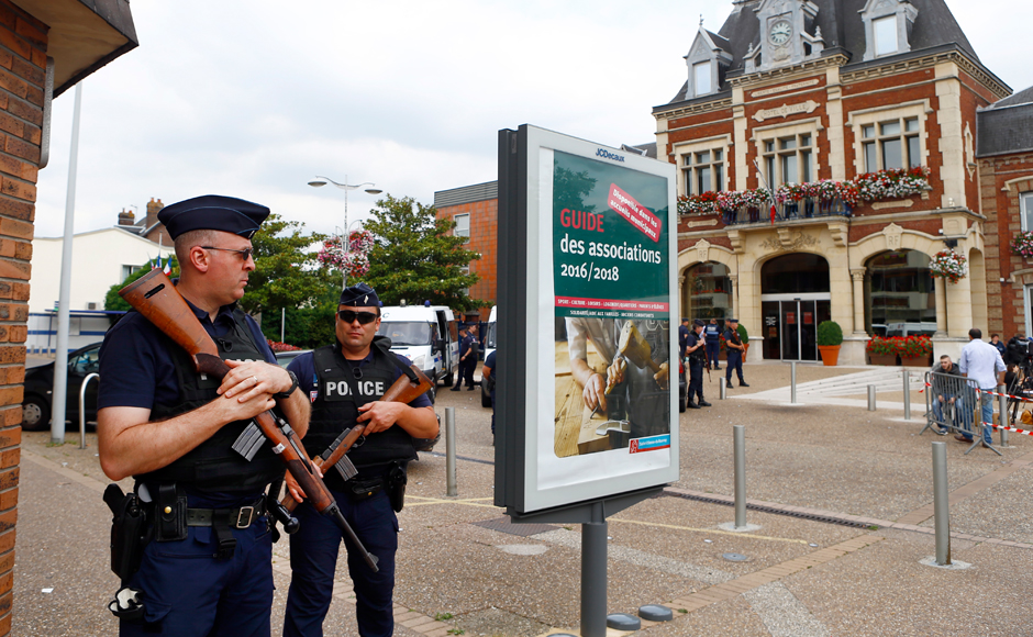 French police officers stand guard in front of the Saint-Etienne-du-Rouvray's city hall, Normandy, France, after an attack on a church that left a priest dead, Tuesday, 26 July, 2016. Two attackers invaded a church Tuesday during morning Mass near the Normandy city of Rouen, killing an 84-year-old priest by slitting his throat and taking hostages before being shot and killed by police, French officials said. AP /Francois Mori