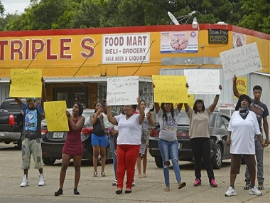 "Family and friends of Alton Sterling protest on the corner of Fairfields Ave. and North Foster Drive Tuesday afternoon, July 5, 2016, after was fatally shot in an altercation with Baton Rouge Police just after midnight, in the parking lot of the Triple S Food Store, in Baton Rouge, La. They chanted things including ""Hands up, don't shoot!"" Officers responded to the store about 12:35 a.m. Tuesday after an anonymous caller indicated a man selling music CDs and wearing a red shirt threatened him with a gun, said Cpl. L'Jean McKneely. (Travis Spradling/The Advocate via AP)"