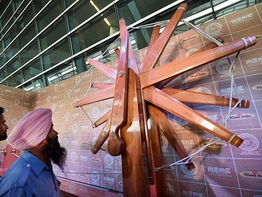 Visitors look at the world's largest wooden charkha at T-3 Departure Forecourt, IGI Airport in New Delhi. PTI