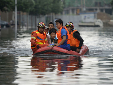 Rescuers use rafts to ferry people from flood-hit areas. AP