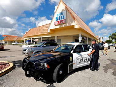 A Fort Myers police officer is seen at a parking lot of Club Blu after the shooting in Fort Myers, Florida. Reuters