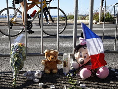A man cycles past a bouquet of flowers, stuffed toys and a French flag placed in tribute to victims. Reuters