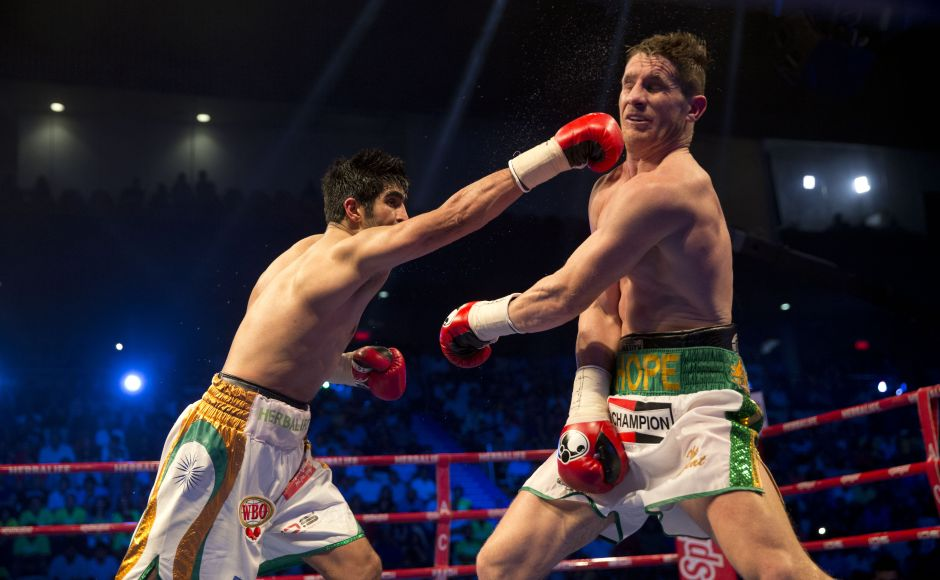 Indian boxer Vijender Singh, left, throws a punch at Australia's Kerry Hope during their fight for the WBO Asia Pacific Super Middleweight title in New Delhi, India, Saturday, July 16, 2016. (AP Photo/Tsering Topgyal)