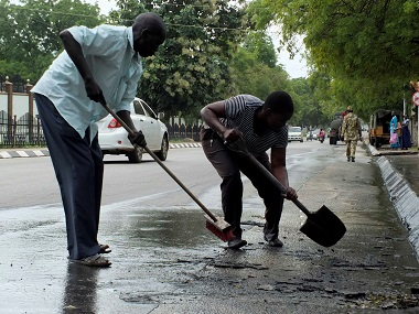 South Sudan civilians clean the streets of dried blood from an unidentified soldier who was killed following the recent fighting outside the Presidential State House in Juba. AFP