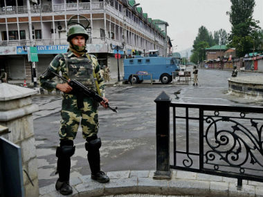 Police official guards the are before curfew was lifted. File photo. PTI
