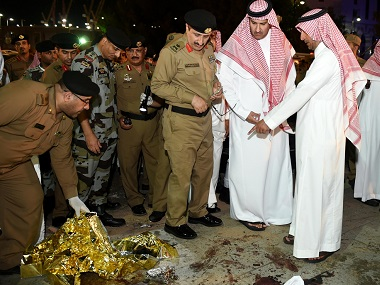 Saudi Emir of Medina Faisal bin Salman bin Abdulaziz (2R) and security officers look at blood stains on the ground after a suicide attack outside the Prophet's Mosque in Medina. AFP