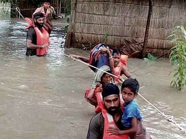 Chirang: Army soldiers rescue flood affected villagers , at Chirang district in Assam on Monday. PTI Photo Pitamber Newar(PTI7_25_2016_000269B)