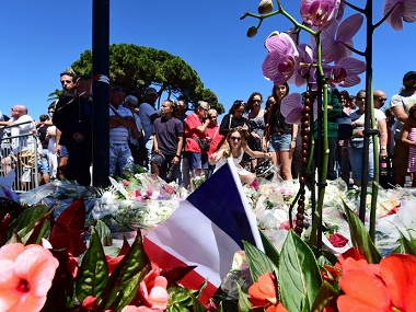 Members of the public lay flowers at a make-shift memorial site in Nice, in tribute to victims of the deadly Bastille Day attack. AFP.