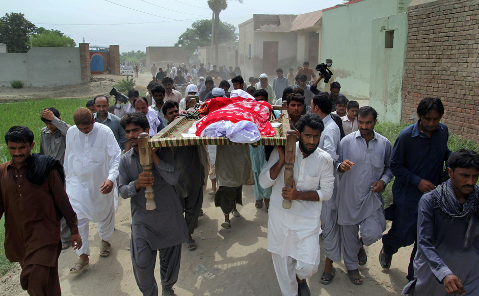 """Relatives and local residents carry the coffin of the late model Qandeel Baloch in Shah Sadar Din village, near Dera Ghazi Khan, Pakistan, after her brother strangled her to death for """"family honour"""" because she posted """"shameful"""" pictures on Facebook. Photo: AP."""