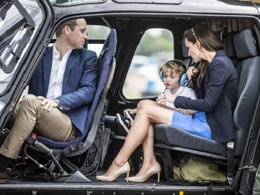 Britain's Prince George (2nd L) sits in a 'Squirrel' helicopter with his mother Catherine, Duchess of Cambridge and father Prince William during a visit to the Royal International Air Tattoo at RAF Fairford in western England. AFP