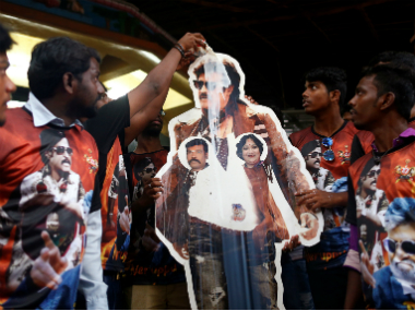 Fans pour milk on a cutout of actor Rajinikanth outside a temple on the eve of the release of Kabali. AP