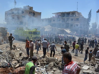 Smoke rises while people gather at a damaged site after two bomb blasts claimed by Islamic State hit Qamishli. Reuters
