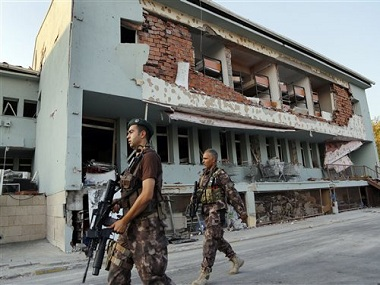 Turkish special forces policemen walk in front of their damaged base, which was attacked by the Turkish warplanes during the failed military coup last Friday, in Ankara, Turkey, Tuesday, July 19, 2016. The violence surrounding the Friday night coup attempt claimed the lives of 208 government supporters and 24 coup plotters, according to the government. Turkey says Fethullah Gulen, a U.S.-based Muslim cleric, was behind the coup and has demanded his extradition. Gulen has denied any knowledge of the failed coup. (AP Photo/Hussein Malla)