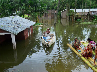 People use makeshift boats to commute in Assam. PTI