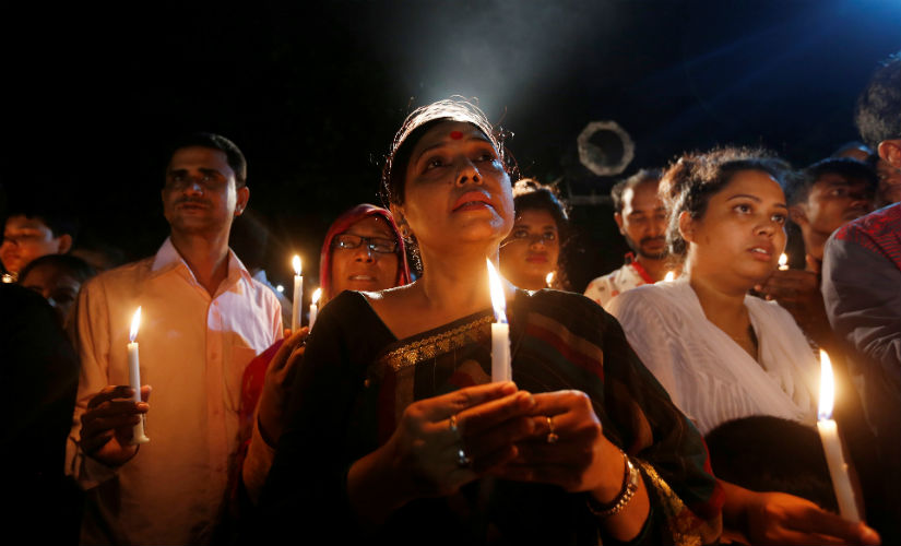 People attend a candle light vigil for the victims of the attack. Reuters