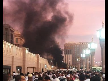 People stand by an explosion site in Medina, Saudi Arabia. AP