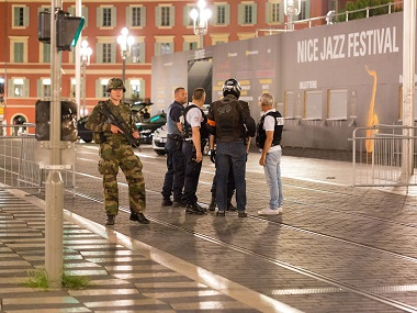 Police officers and a soldier stand by the sealed off area of an attack after a truck drove on to the sidewalk and plowed through a crowd of revelers who'd gathered to watch the fireworks in the French resort city of Nice on Thursday night. AP